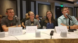 WSU students in a knowledge competition at a table with nametags and microphone.