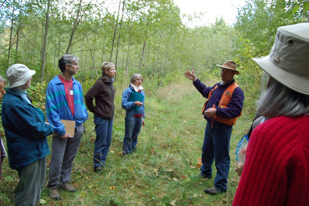 Perleberg gestures to a stand of trees with a small group out in the field.