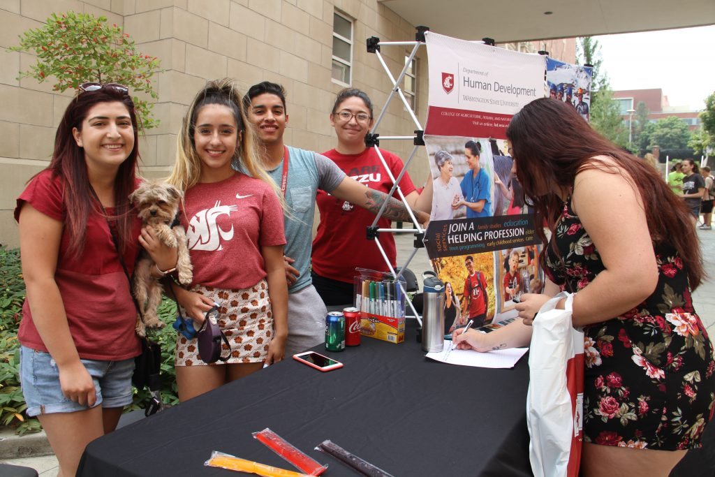 Human Development students pose with a dog at their booth as students sign the guest sheet.