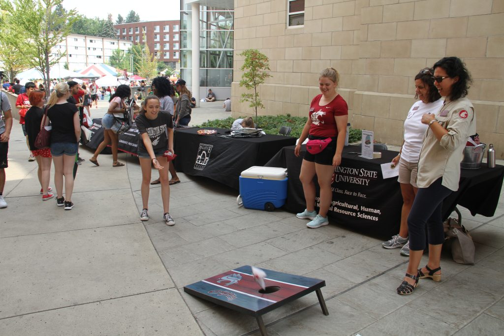 A student makes a beanbag toss along a row of booths and passersby.