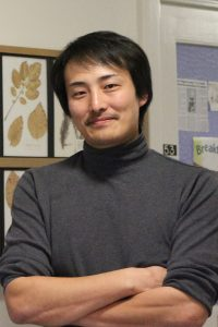 Kiwamu Tanaka stands with his arms crossed in front of a photo of leaves.