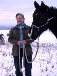 Angela Reitmeier stands next to a horse in a snow-covered field.