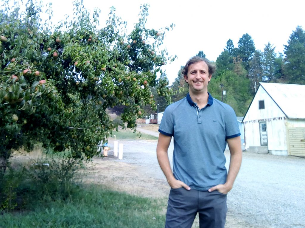Tobin Northfield, outside at a research station, next to apple trees.