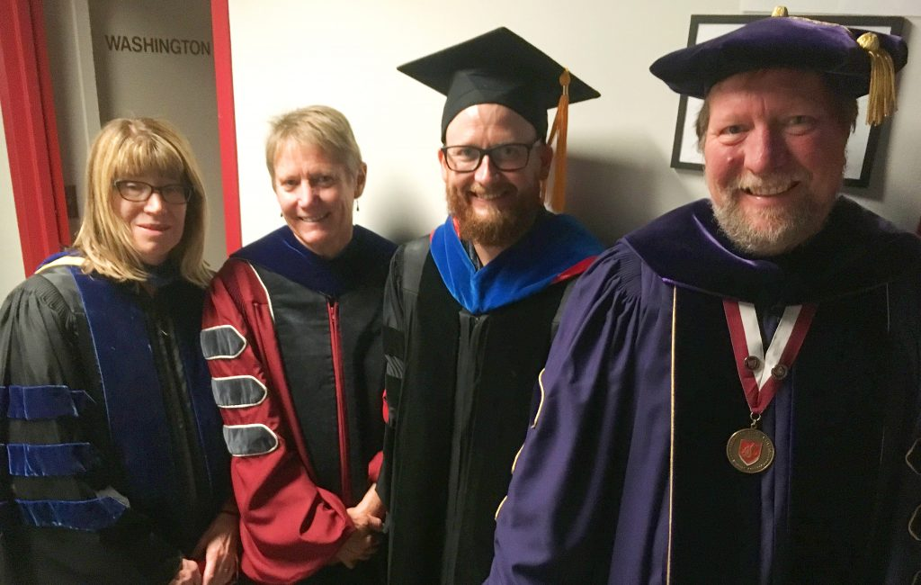 Four faculty members, in robes, pose in a hallway.