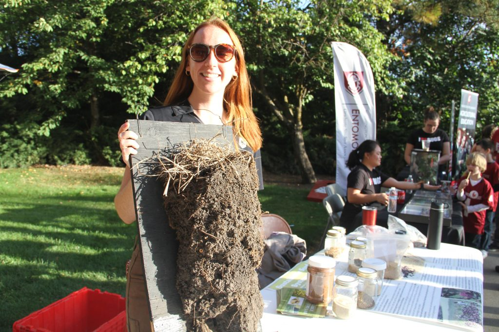 A graduate student shows off a soil sample, standing at a table.