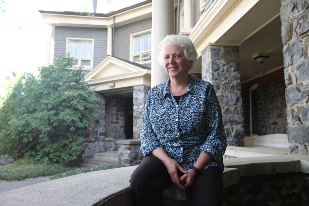 Deb Nelson sits on the porch of the grey-stone Stevens Hall.