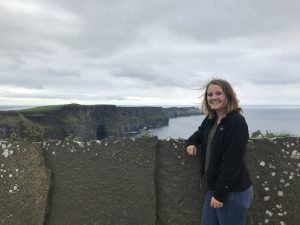Doonan leans against a stone wall overlooking dramatic cliffs in the background.