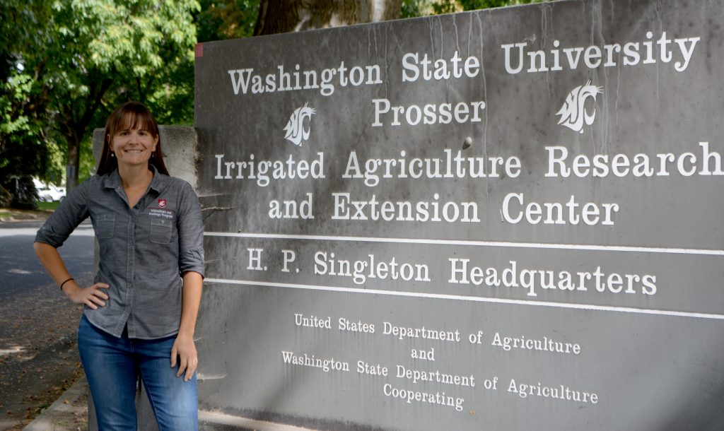 Moyer stands next to a sign at the entrance of WSU IAREC research center.