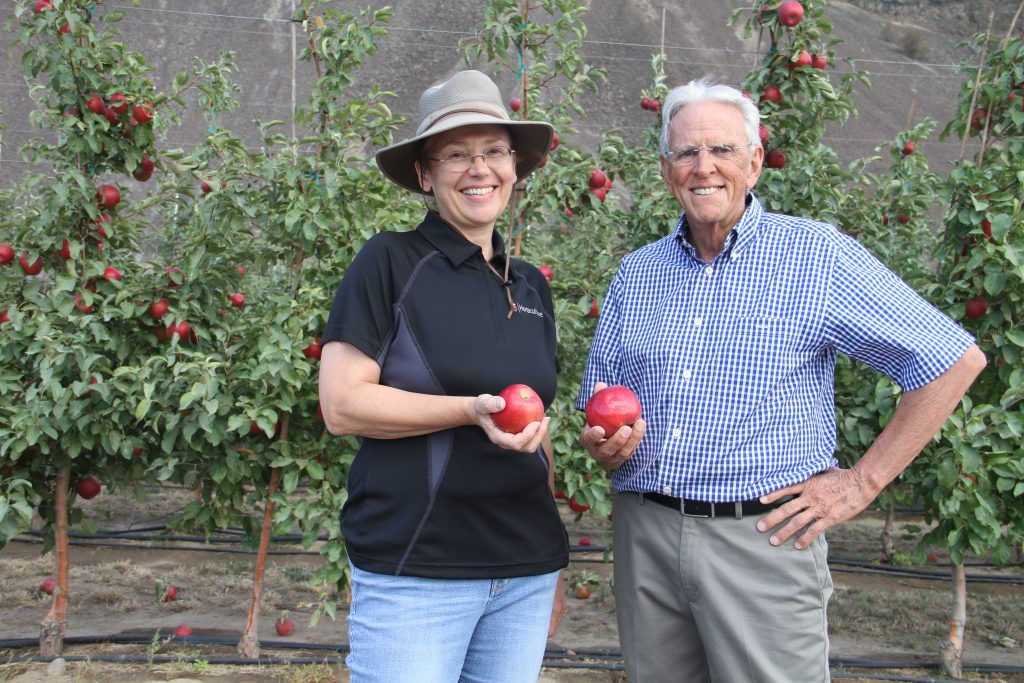 Evans. left, and Barritt hold red apples in front of a wall of trees.