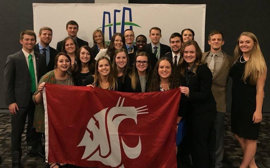 Group photo of WSU students, holding a crimson WSU flag, at the AFA conference.