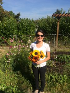 Brenda Madrid holds a bouquet of sunflowers in a garden.