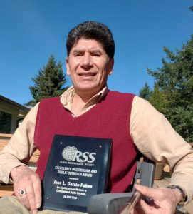 Dr. García-Pabón, seated outdoors, holding his award.