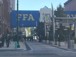 A huge blue banner with the letters FFA hangs from a pedestrian bridge while many people wearing blue corduroy coats walk under it.