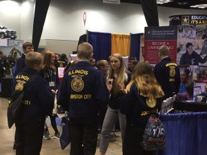Maya Wahl is surrounded by students wearing blue corduroy FFA coats on a convention floor.