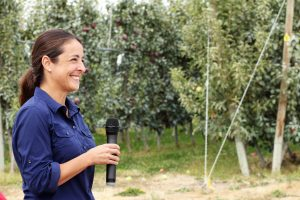 Sallato holding microphone in orchard.