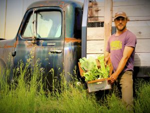 Farmer holding a box of produce in front of an antique farm truck.