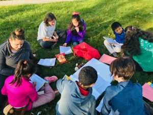 A circle of children, teens and adults work on art together, outdoors.