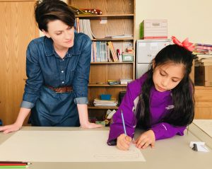A standing teacher at left overlooks a student creating artwork at a table.