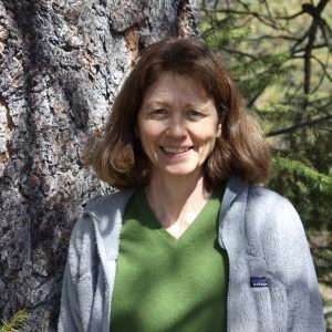 Profile photo of Marcia Ostrom outdoors near a tree.