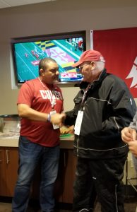 Wright shakes hands with Olson in a room with a TV and WSU flag in the background.