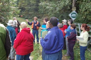 Tour group at a forest listens as Perleberg, in orange vest and field hat, gestures.