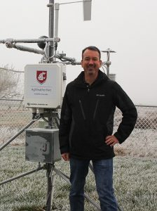 Brown, in black coat, stands in front of weather station with Coug logo.