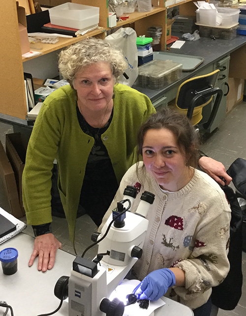 Photo of Carris standing next to a seated Harper, in front of a microscope in a lab.