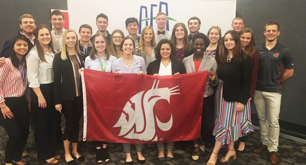 Group photo showing 21 students holding the Cougar flag at the AFA conference, with AFA banner in background.