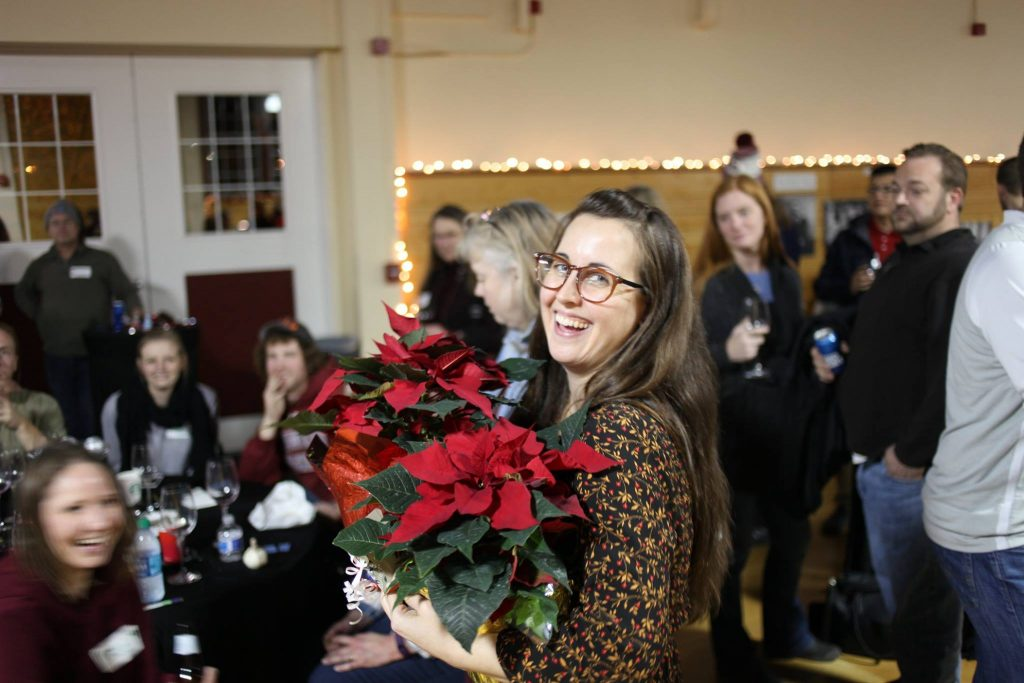 A woman holds a poinsettia, smiling at the camera