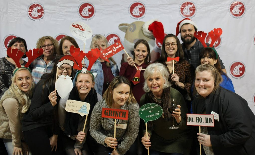 A group of guests from a department pose with props at the holiday photo booth,