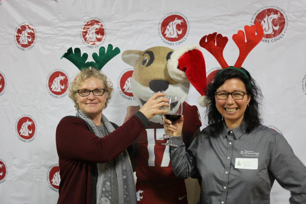Two party guests, wearing festive antlers, clink glasses in front of the Coug mascot.