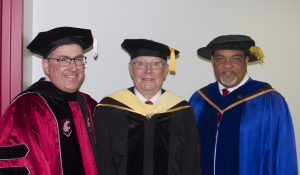 Photo of WSU President Kirk Schulz, Dr. Cook, and Dean Wright, in ceremonial academic robes, in a hallway.