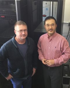 See, left, and Zhang, right, in a room of computer servers, facing the camera.