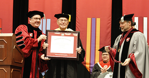 Cook, center, holds up his honorary certificate during the commencement ceremony, flanked by Schulz, Blankenship.