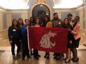 A group of students holds a WSU Coug logo flag in a brightly lit room.