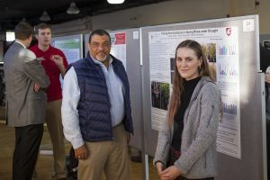 Wright and Hickey pose in front of a research poster, with two other people talking about research behind them.
