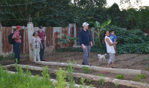 5 adults, one holding a small boy, and a little dog walk around a garden surrounded by corrugated metal fencing. The garden rows are separated by cinder blocks.