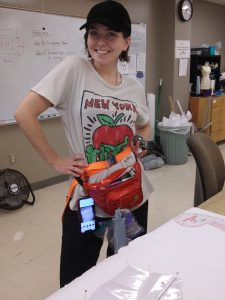 Madison wears a hat and t-shirt, posing with a phanny pack stuffed full of thread, needles, and other sewing and design equipment.