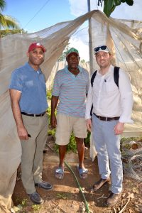 The 3 men pose under a shade tarp in a garden. There are green plants in the background.