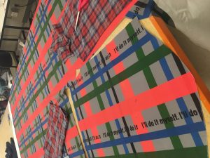 "Colorful plaid fabric with the words ""I can do it myself."" written over and over across it."