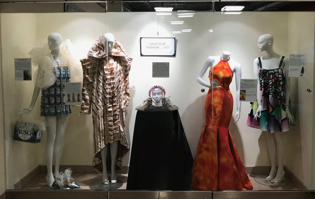 Fashions on display in a case, on manequins and a stand.
