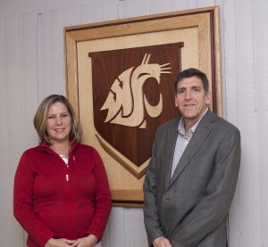 Jill McCluskey and Scot Hulbert pose in front of a WSU shield.