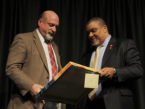 Miller, left, accepts a gift of artwork from Dean Wright.