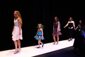 A woman in a white dress, a little girl in a blue dress, then a woman in a blue floral print dress walk on a white catwalk against a black background. They are followed by two designers holding bouquets.