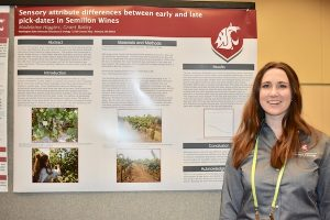 Student stands in front of her research poster at convention.