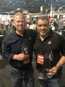 Warner and Wright pose for a photo with wine glasses in hand and many people milling about in the background.