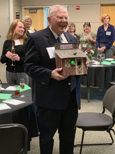Burcalow, surrounded by friends and family, accepts a personalized birdhouse gift in an awards ceremony.