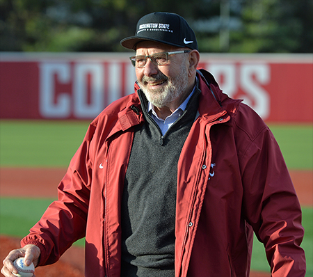 Ken Casavant in Cougar hat and red jacket on baseball field.