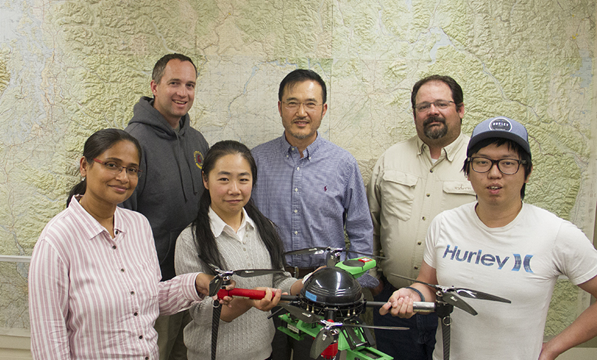 Group photo of scientists with front row holding drone