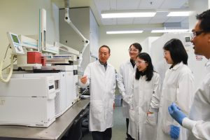 Lei and 4 colleagues all wear white lab coats and look at a complex looking white plastic machine.